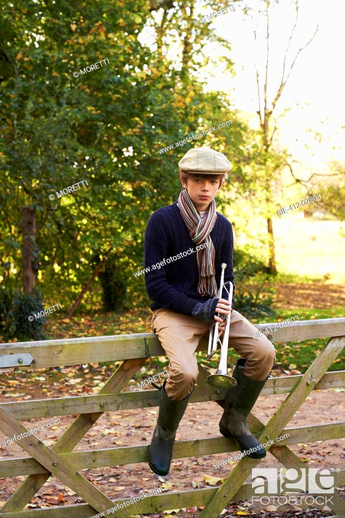 Stock Photo: Teenage boy holding trumpet on wooden fence.