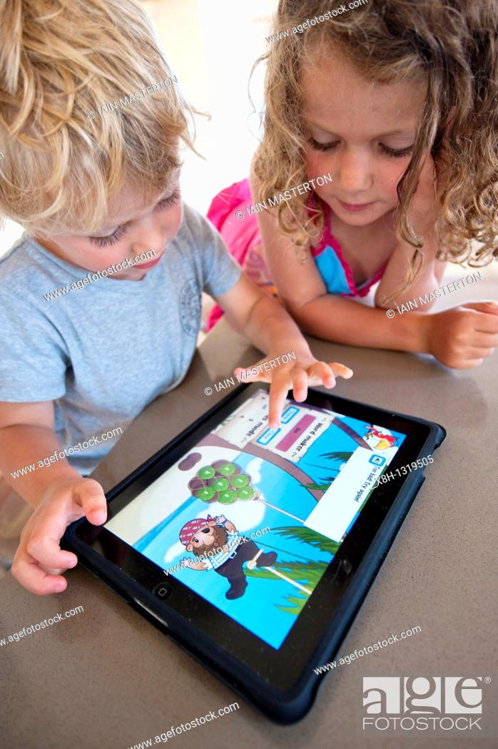 Stock Photo: Children playing computer game on an iPad tablet computer.