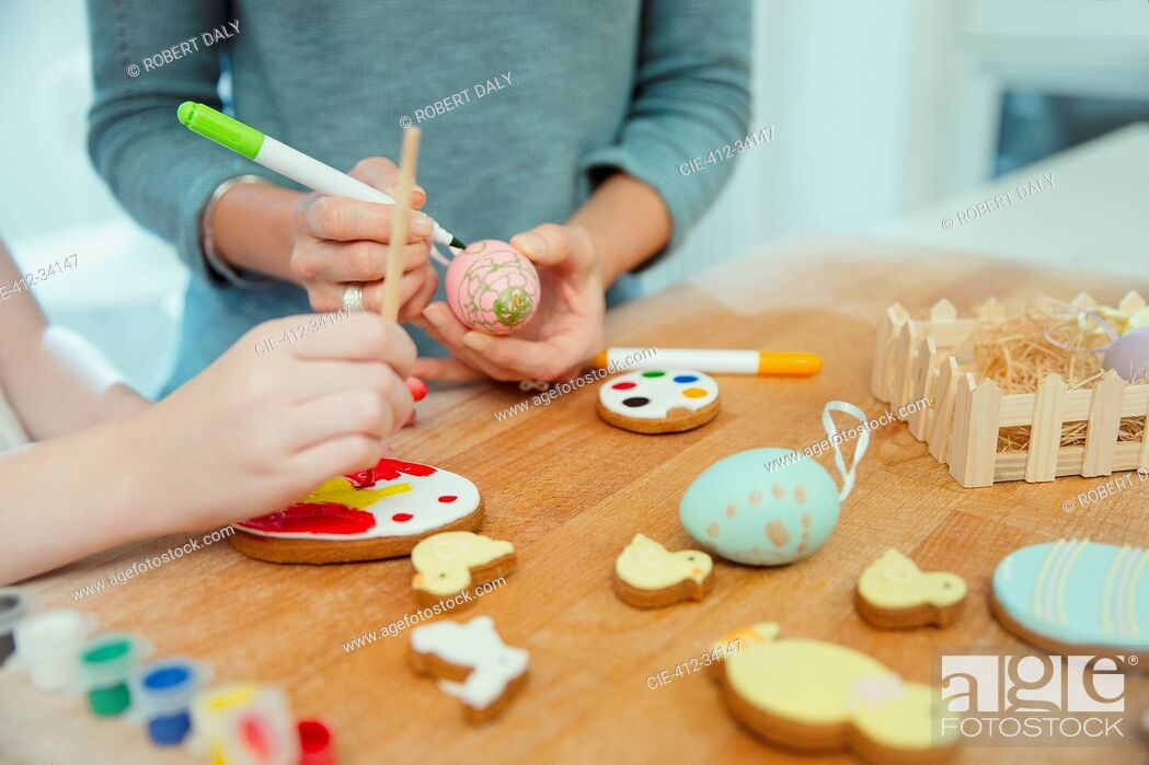 Stock Photo: Close up mother and daughter decorating Easter eggs and cookies.