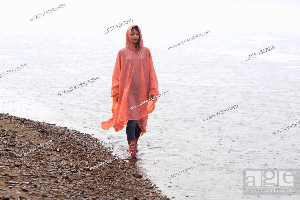 Imagen: Woman wearing raincoat walking at lakeshore during rainy season.