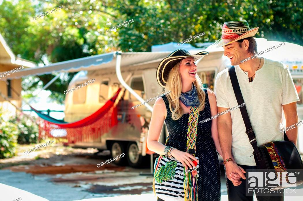 Stock Photo: Couple standing in front of converted boutique airstream trailer.