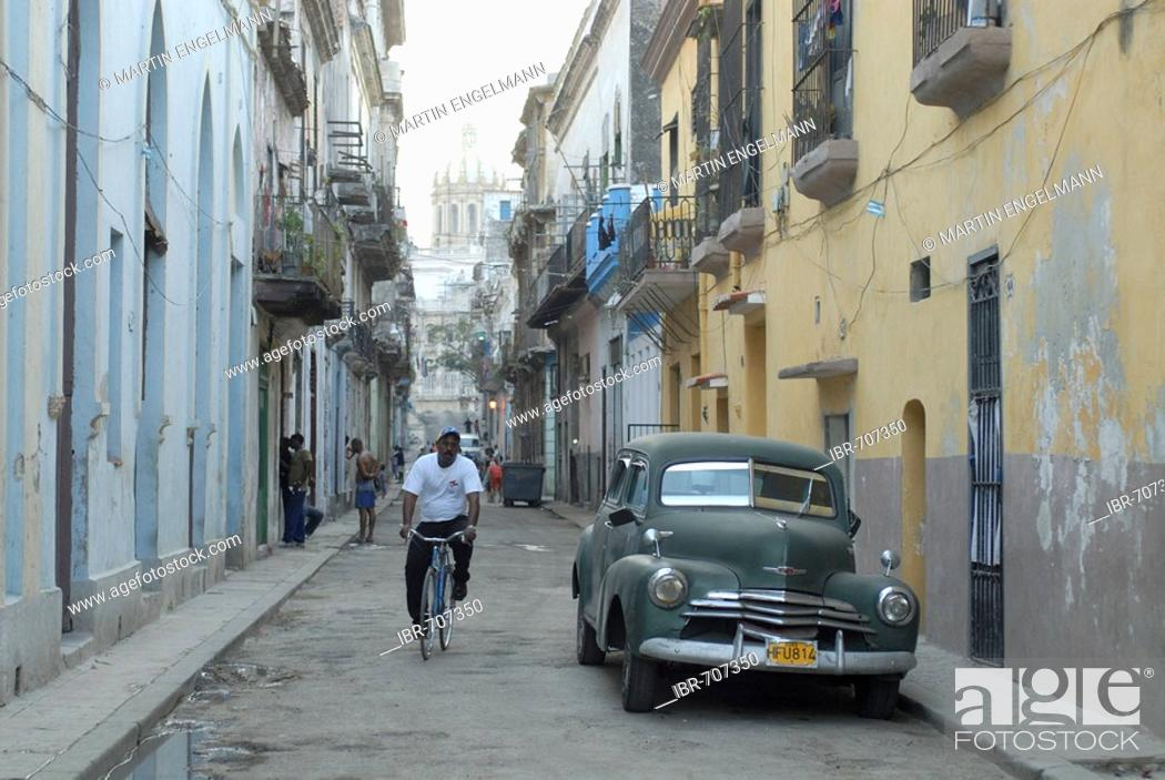 Stock Photo: Vintage car and cyclist in an alley in the old part of Havana, Cuba, Caribbean.