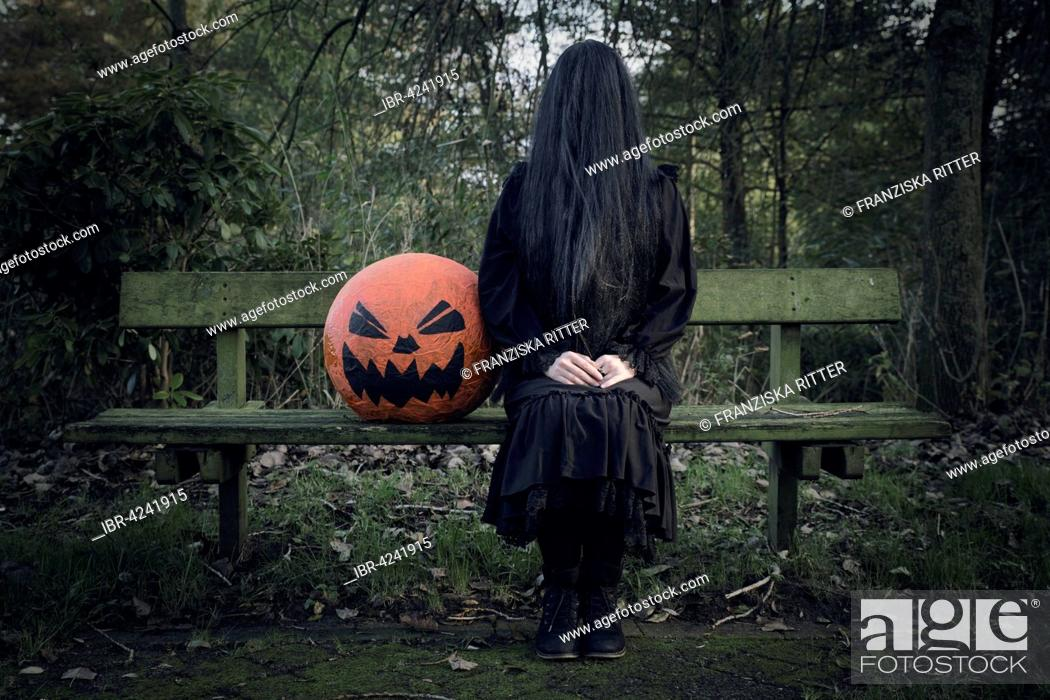 Imagen: Woman in black, face covered with long black hair, sitting beside a pumpkin, ghost woman with pumpkin head, Halloween.