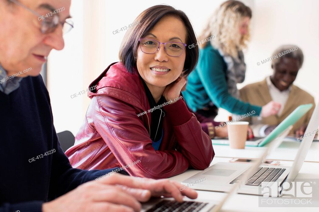 Stock Photo: Portrait smiling, confident senior businesswoman using laptop in conference room meeting.