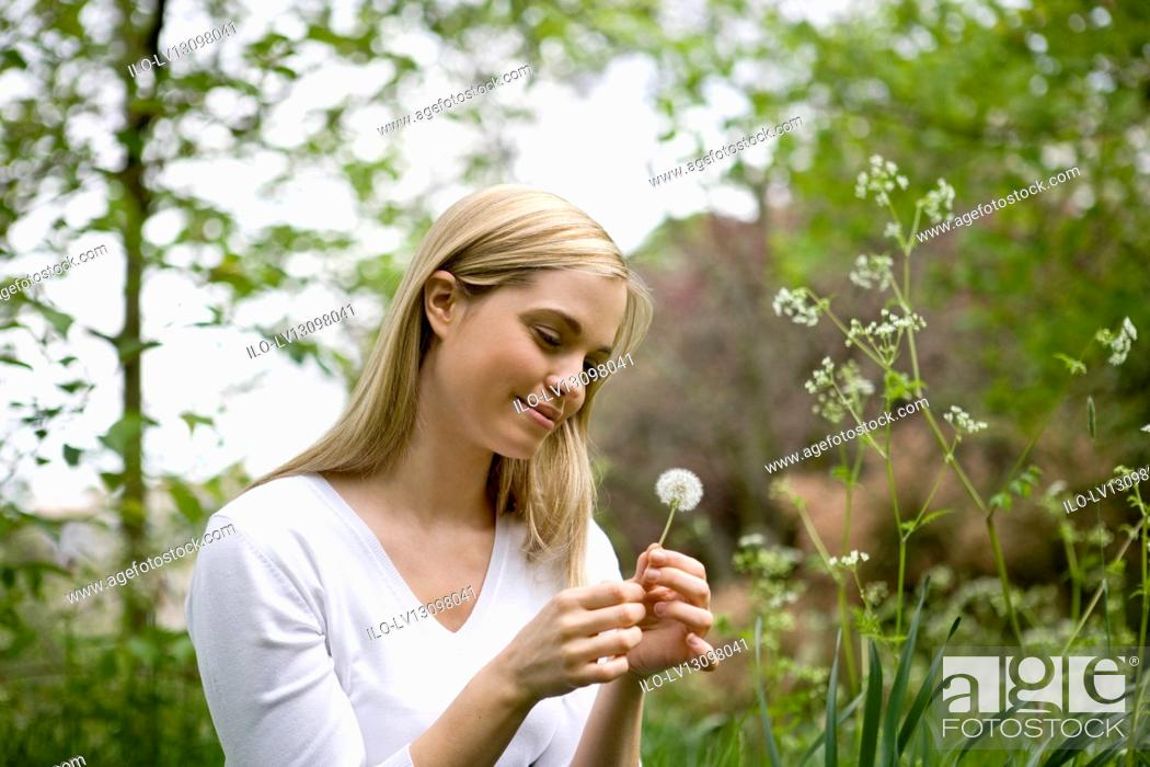 Stock Photo: A young woman looking at a dandelion clock.