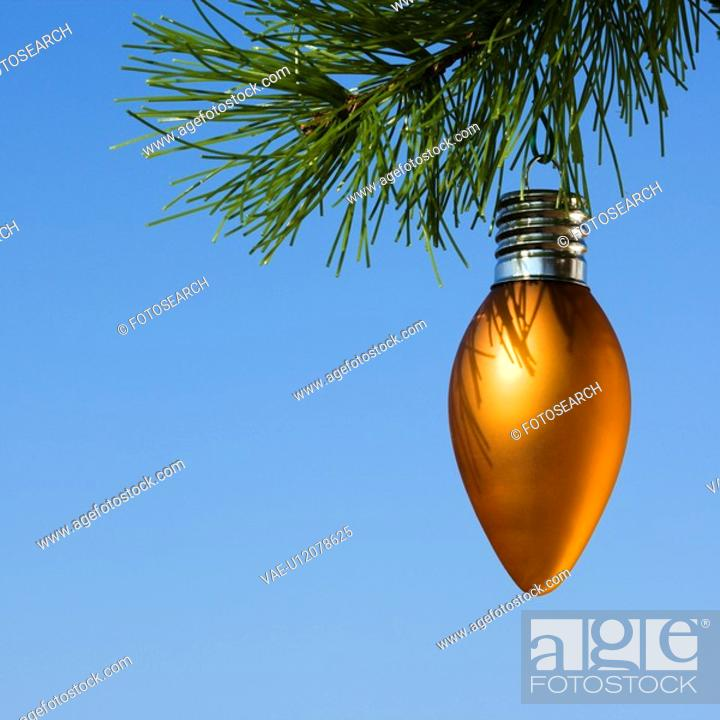 Stock Photo: Orange ornament hanging on Christmas tree branch against blue background.