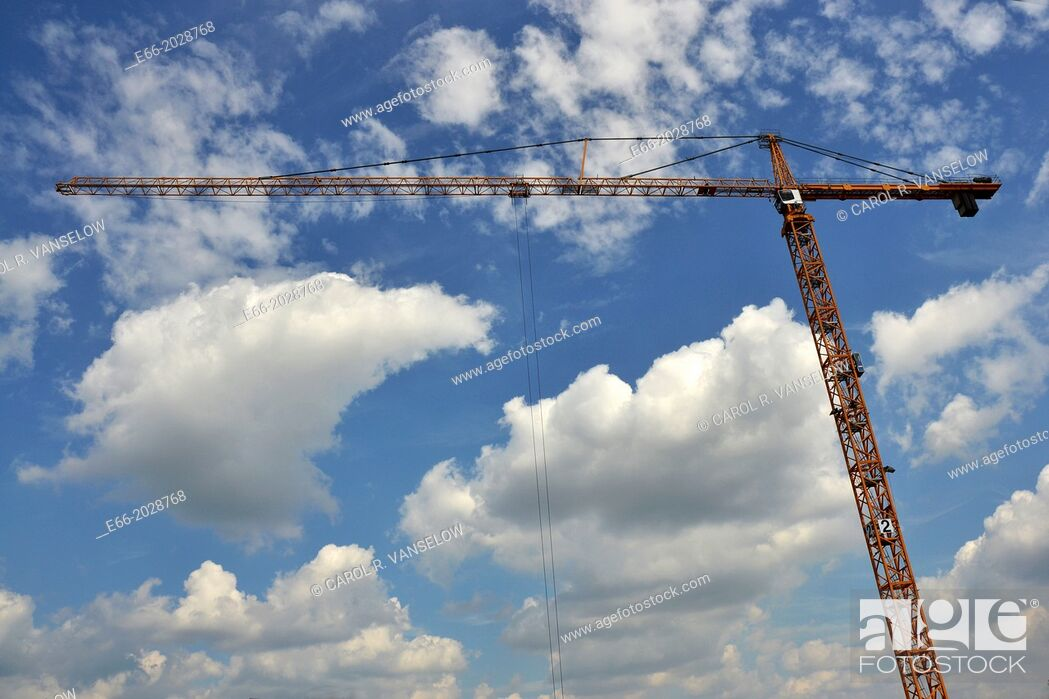 Stock Photo: light blue sky with clouds with building crane running horizontally through the image.