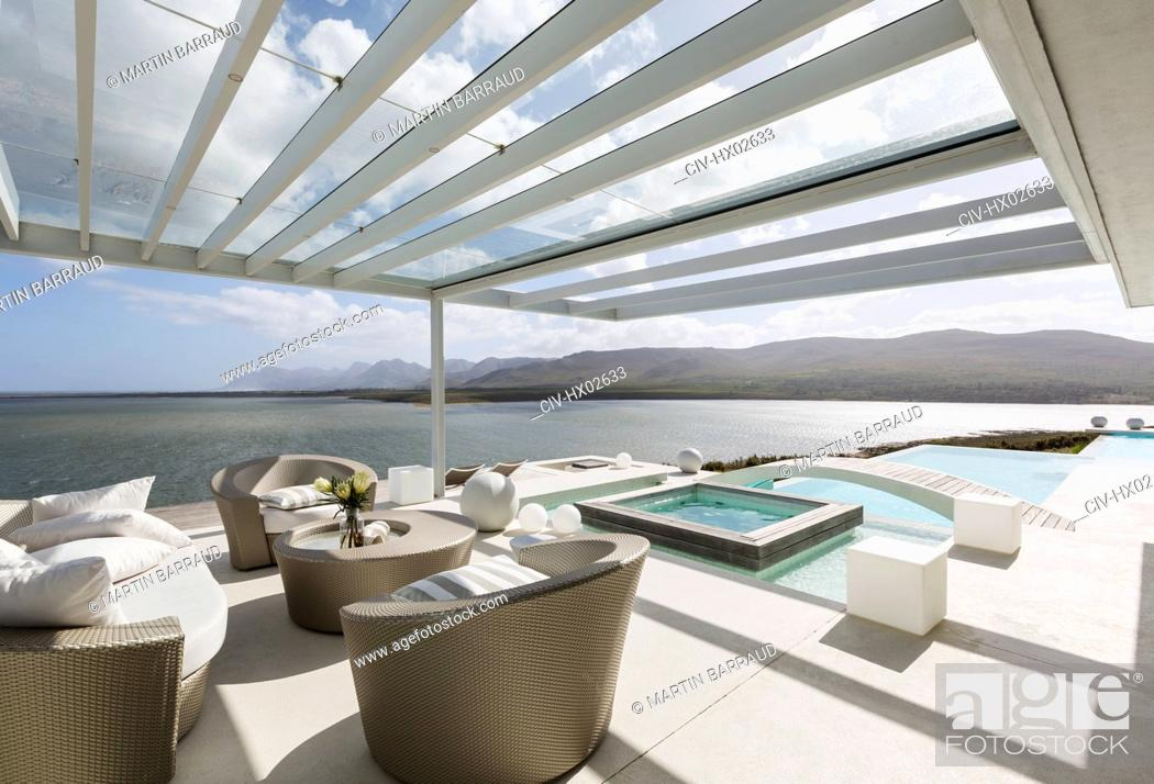 Stock Photo: Sunny modern luxury patio with infinity pool and ocean view.