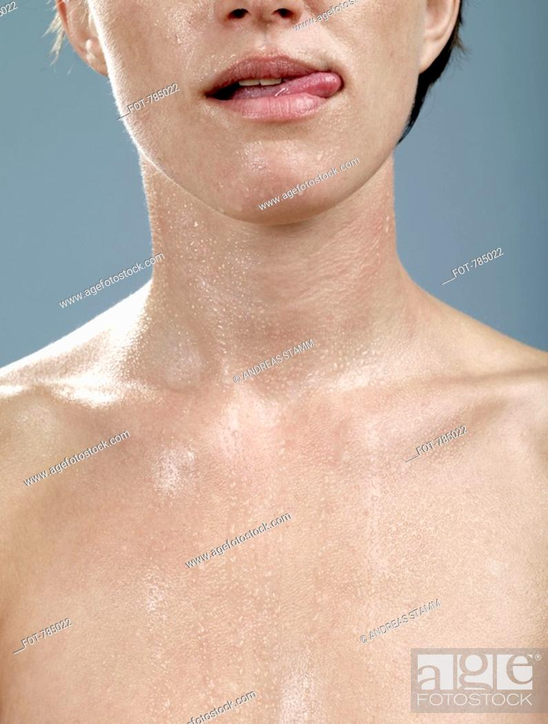 Stock Photo: A woman with wet skin licking her lips.