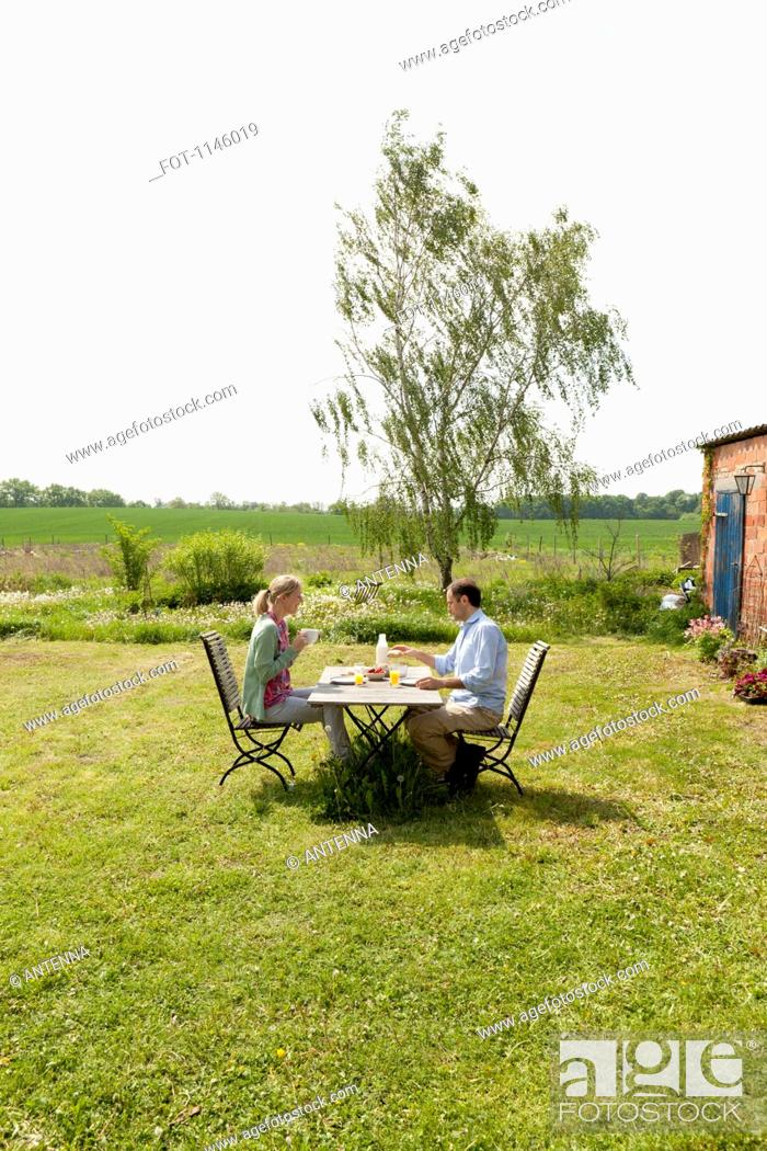 Stock Photo: A couple having breakfast in their backyard.