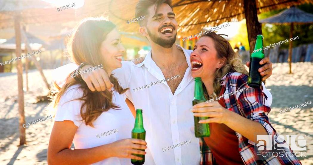 Stock Photo: Beach party with friends. Cheerful young people spending nice time together on the beach and drinking beer.