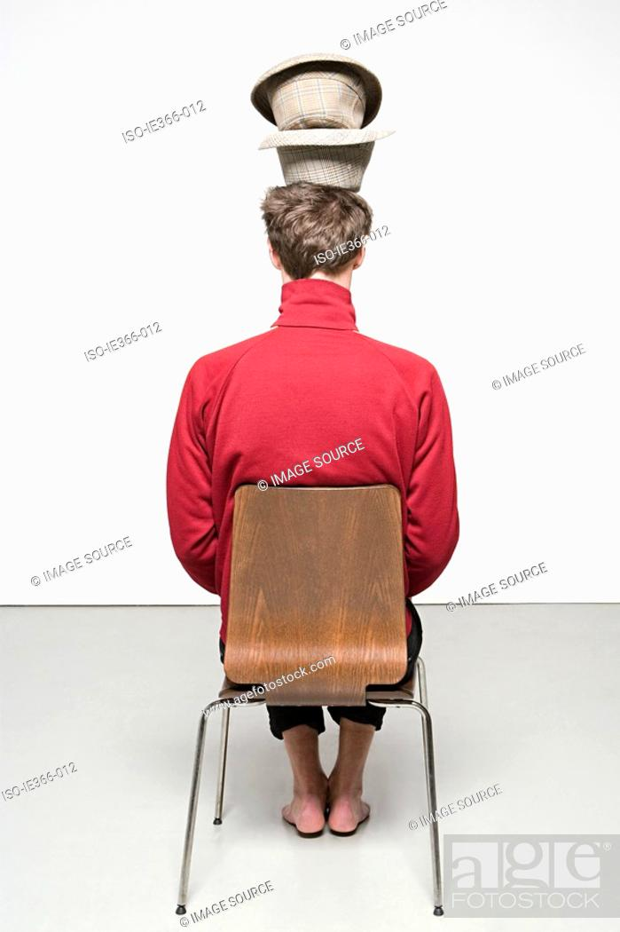 Stock Photo: Rear view of man with hats on his head.