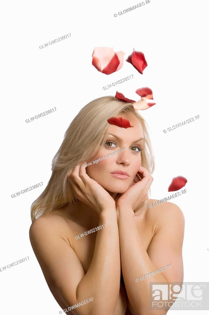 Stock Photo: Rose petals falling on a young woman.