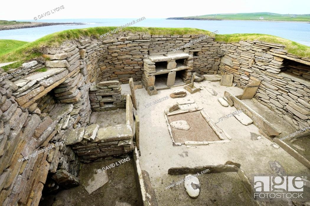 Stock Photo: Skara Brae Stone Age Neolithic village at Skaill, Orkney, Scotland. Interior, box beds, hearth and dresser 3100 BC. House 1 with Bay of Skaill behind.