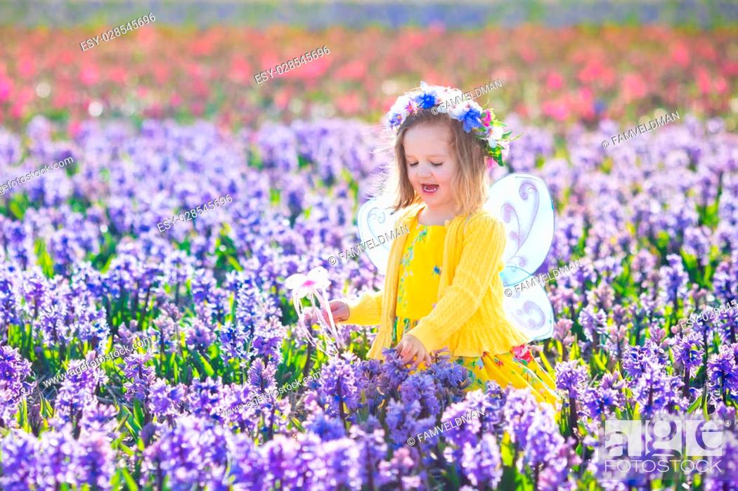 Stock Photo: Beautiful girl playing in blooming hyacinth flower field. Kids princess birthday party with fairy costume, butterfly wings and magic wand.