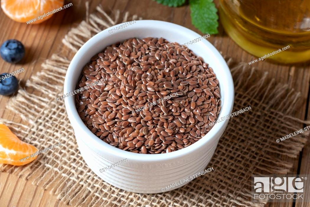 Stock Photo: Flax seeds in a bowl, with oil in the background.