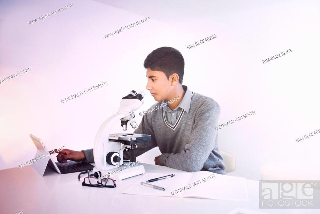 Stock Photo: Fiji Indian boy using digital tablet and microscope.
