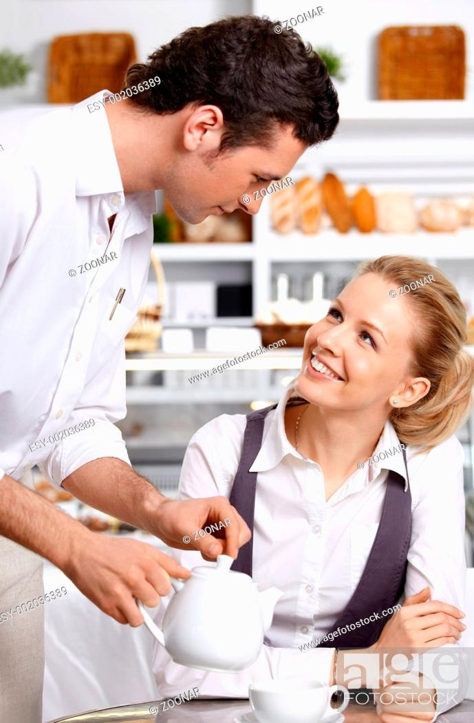 Stock Photo: The young waiter with the client in cafe.