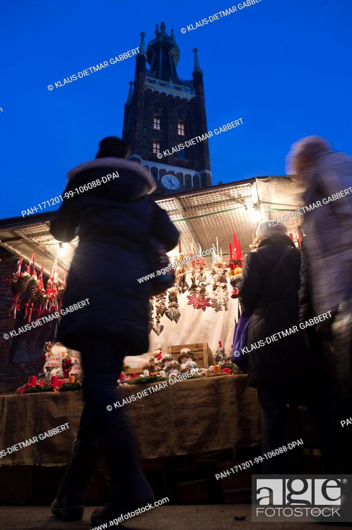 Stock Photo: Visitors walk across the Advent market in Oranienbaum-Woerlitz, Germany, 01 December 2017. The tower of the St. Petri Church can be seen in the background.
