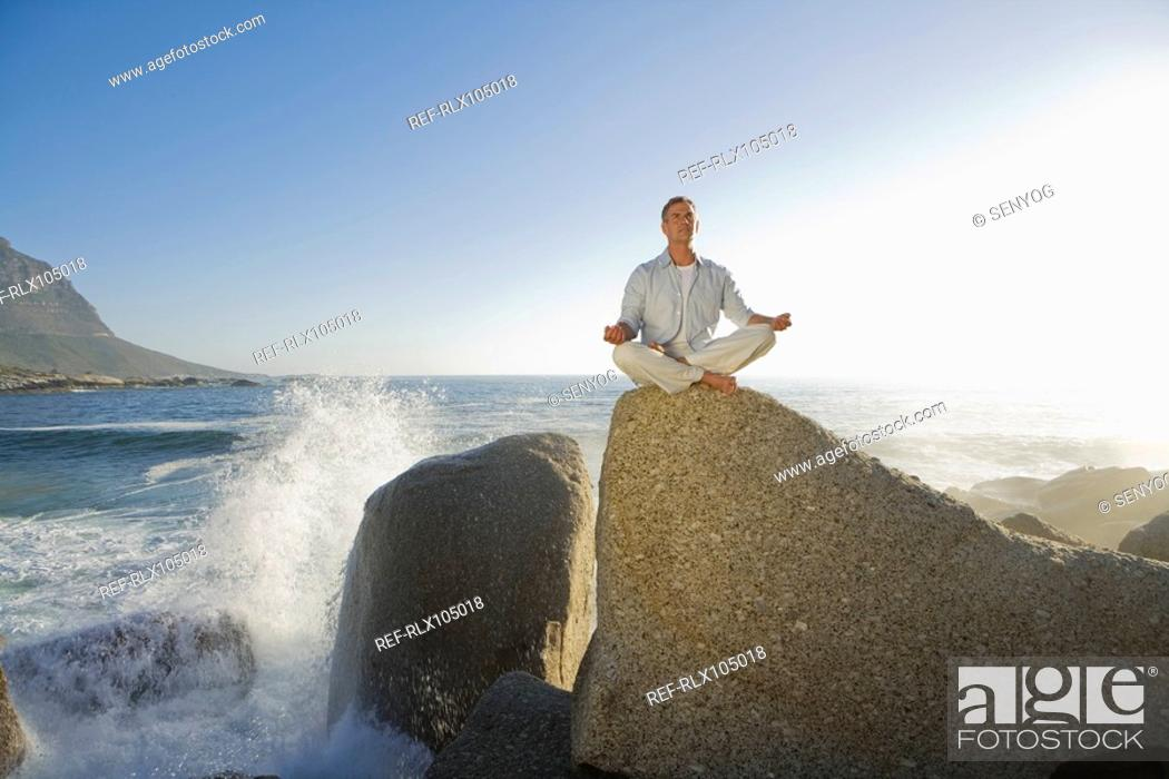 Stock Photo: Mature man sitting doing yoga on top of rock outcrop with waves in background.