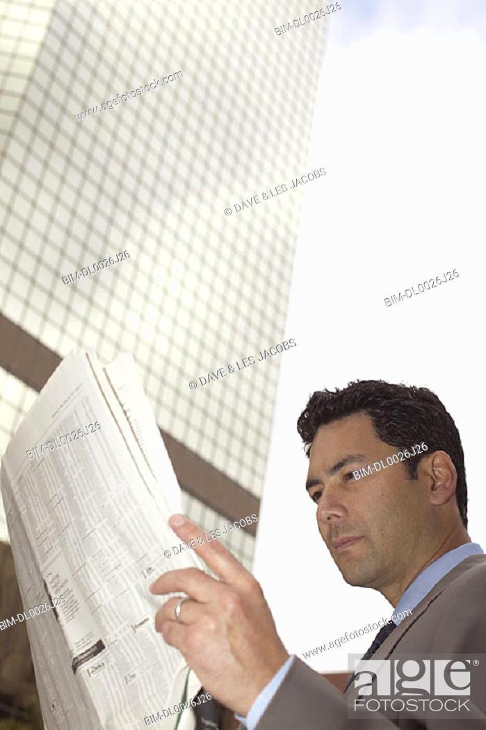 Stock Photo: Businessman reading financial newspaper.