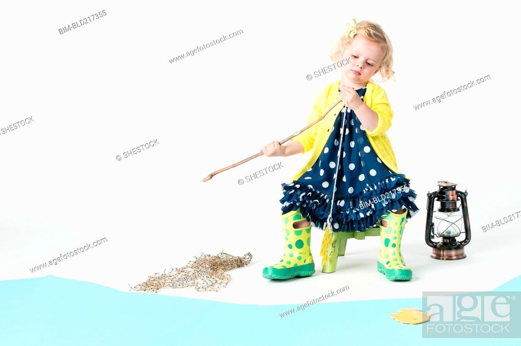 Stock Photo: Girl playing fishing with toy fish.