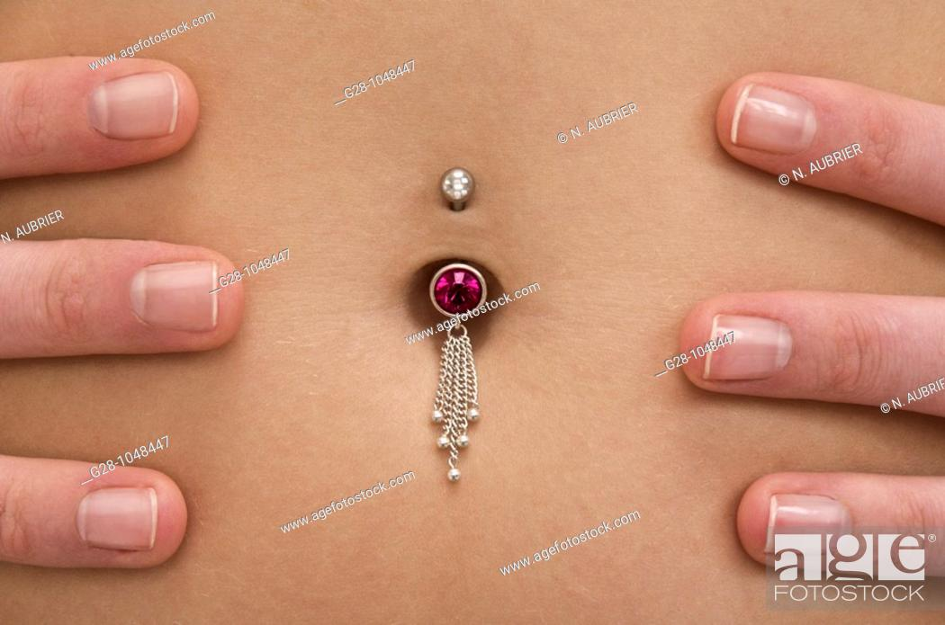 Stock Photo: woman's tummy pierced with jewel close up.