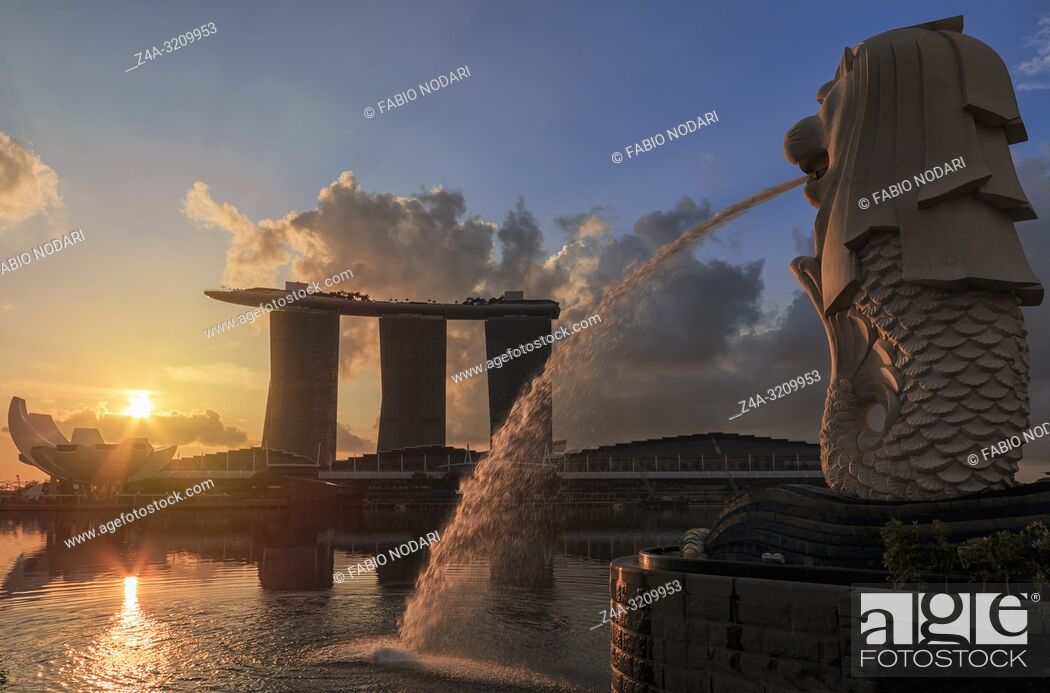 Stock Photo: Sunrise in Singapore with a beautiful view of the Marina Bay Sands, Modern Art Museum, Merlion and other iconic buildings.