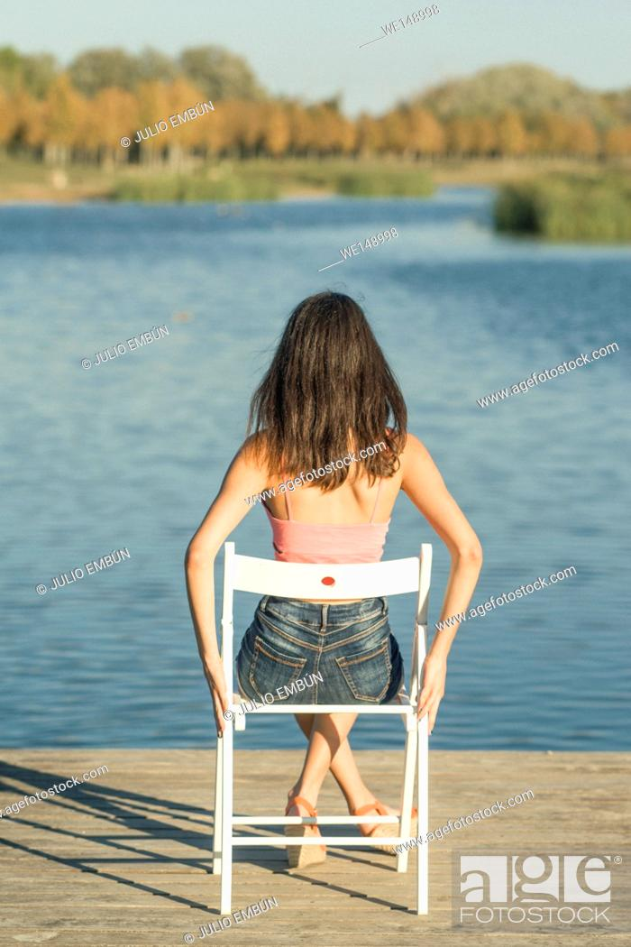 Photo de stock: Young girl sitting on a chair on the dock enjoying the lake at sunset.