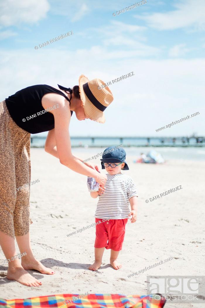 Stock Photo: 2 years old boy with his mother drinking juice at the beach.
