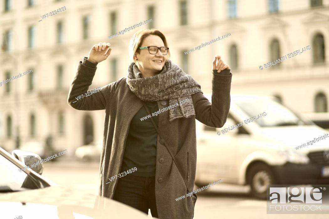 Stock Photo: happy woman with arms up at street in city Munich, Germany.