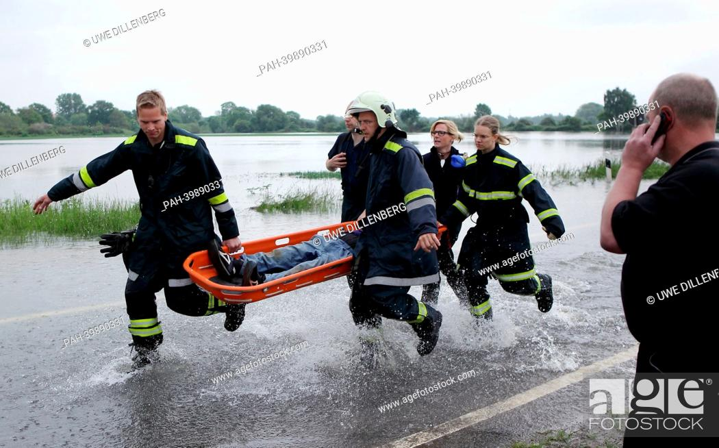 Stock Photo: Firefighters carry a woman on a stretcher in the floodplain of the Leine river in Hanover, Germany, 30 May 2013. The woman had an accident with her bicycle in.