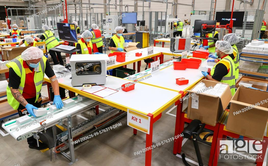 Stock Photo: 26 June 2020, Saxony, Leipzig: DHL employees pack e-cigarettes in a logistics centre jointly operated by DHL and Philip Morris Germany.
