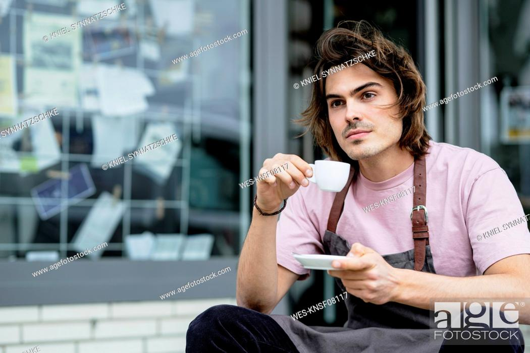 Stock Photo: Thoughtful male barista holding coffee sitting outside coffee shop.