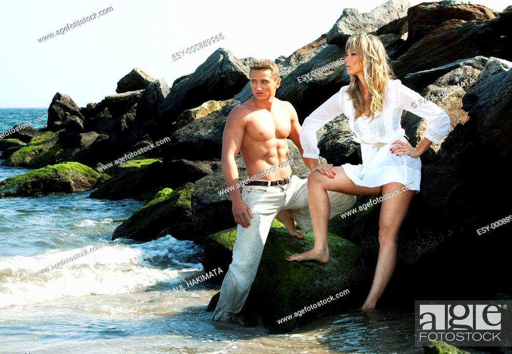Stock Photo: Caucasian guy and girl together on rock formation next to ocean water  Female is wearing long white shirt  Both standing on rocks at the beach  Guy showing.