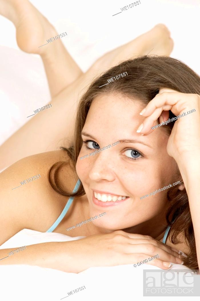 Stock Photo: Caucasian woman in early 20's laying in bed.