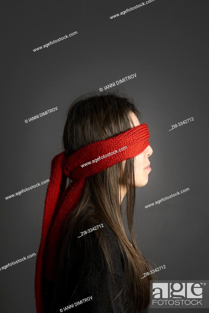 Stock Photo: Young girl with long dark hair blindfolded with red scarf- sode vie.