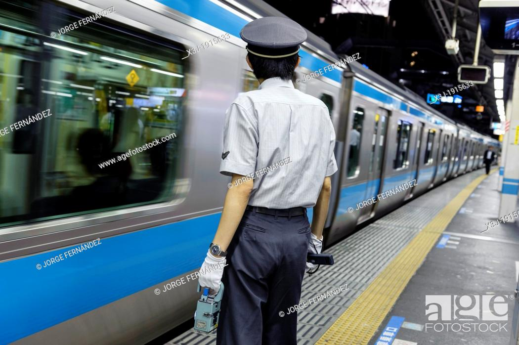 Stock Photo: Metro worker watching the train leaving the station, Tokyo, Japan, Asia.