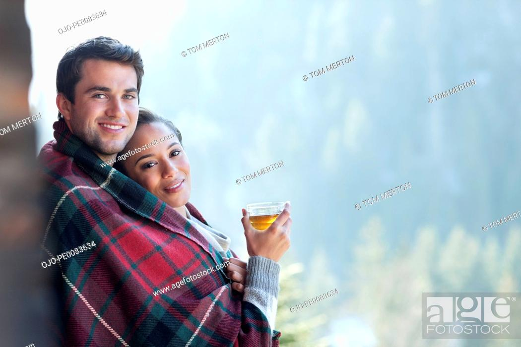 Stock Photo: Portrait of smiling couple wrapped in a blanket and drinking hot cider on porch.