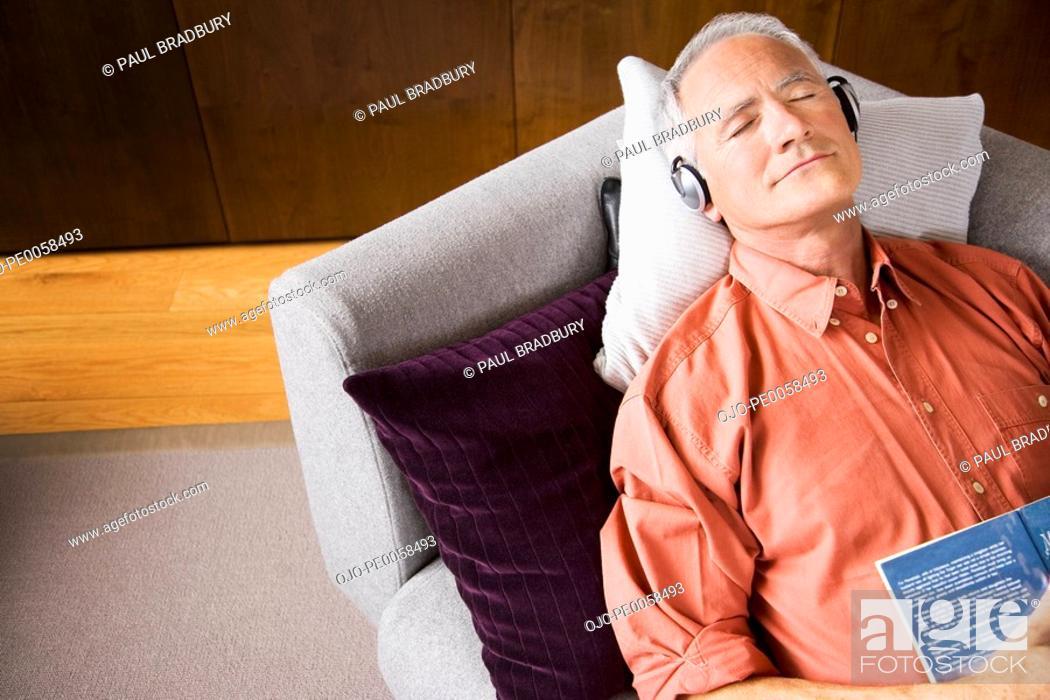 Stock Photo: Man wearing headphones sleeping on sofa with book.