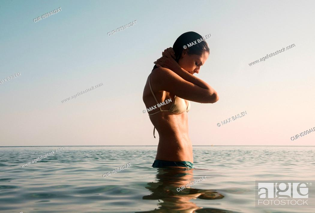 Stock Photo: Beautiful young woman with hands behing neck in sea.