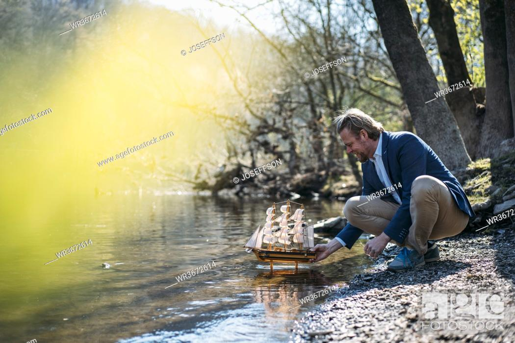 Stock Photo: Businessman crouching while holding model boat at riverbank in park.
