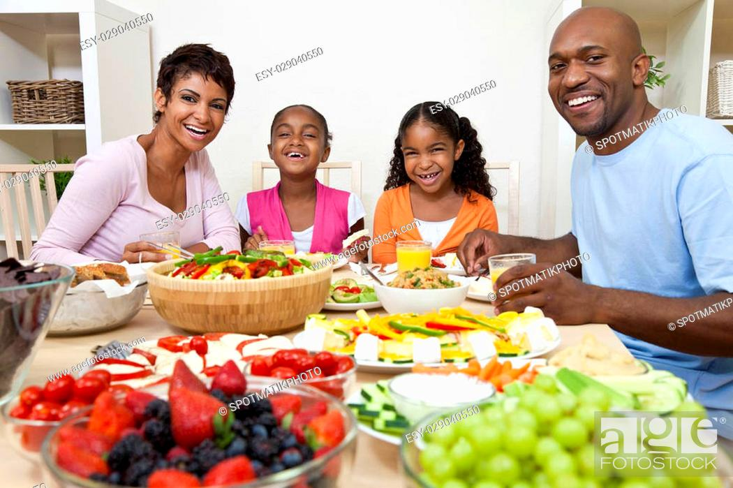 Stock Photo: An attractive happy African American, smiling family of mother, father, two daughters eating salad and healthy food at a dining table.