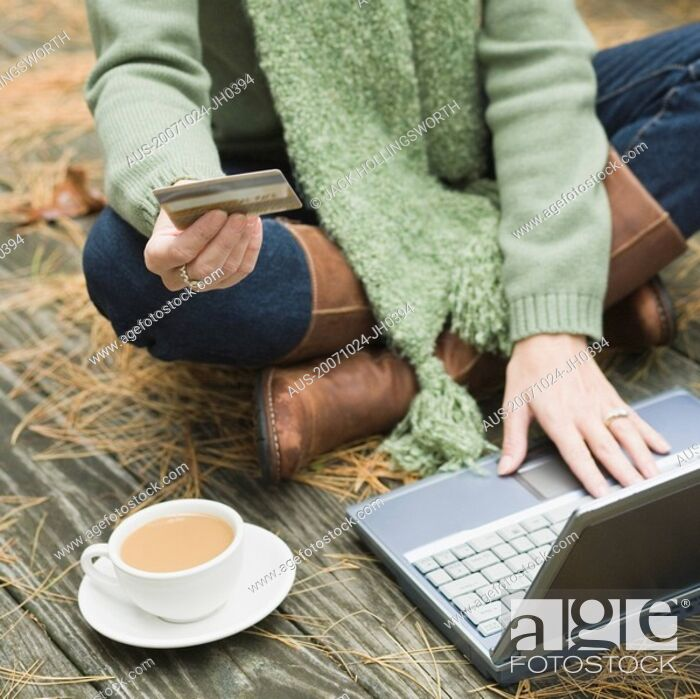 Stock Photo: High angle view of a woman holding a credit card and working on a laptop.