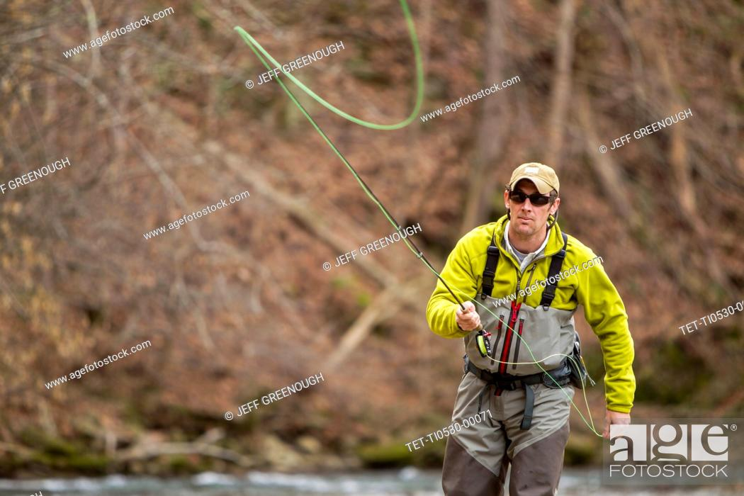 Photo de stock: Young man fly-fishing in river.