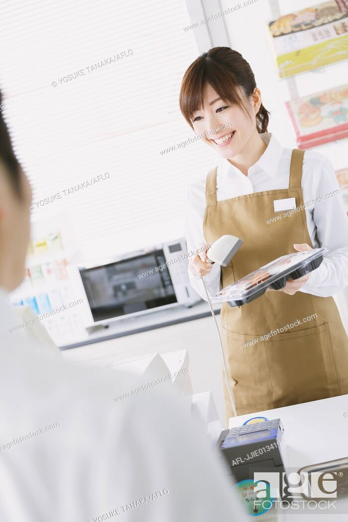 Stock Photo: Young Japanese woman working at convenience store.
