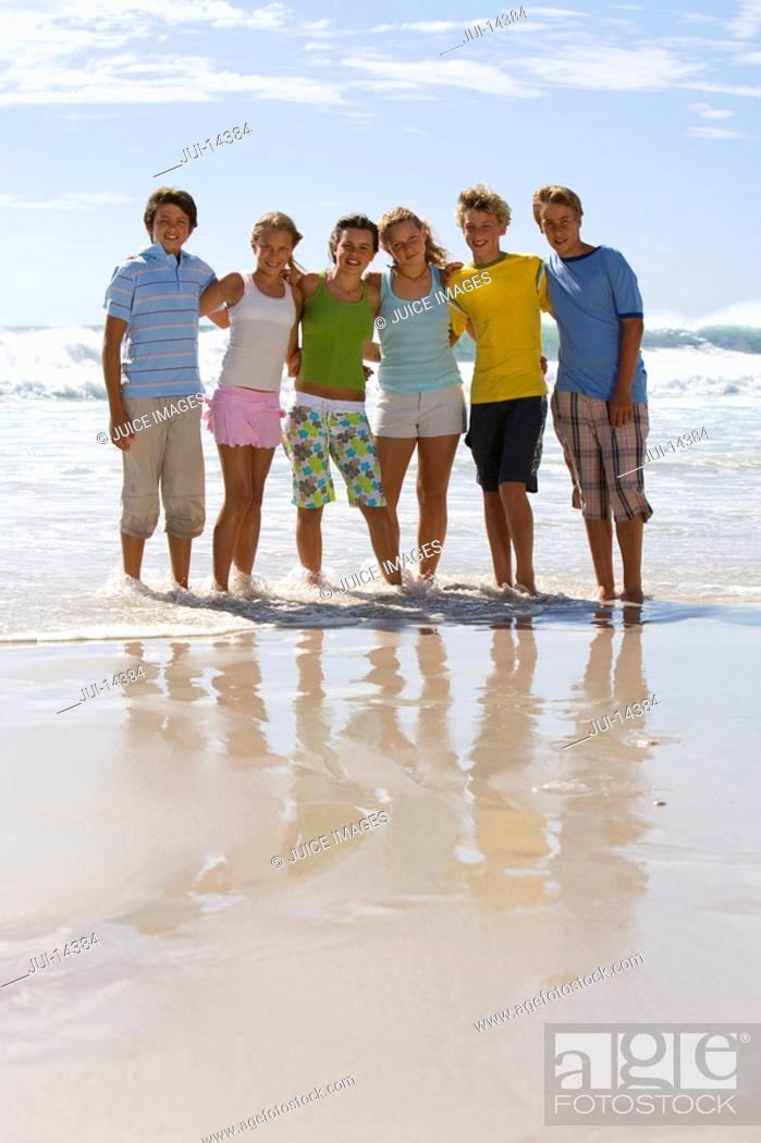 Stock Photo: Group of teenagers 14-16 arm in arm on beach, smiling, portrait.