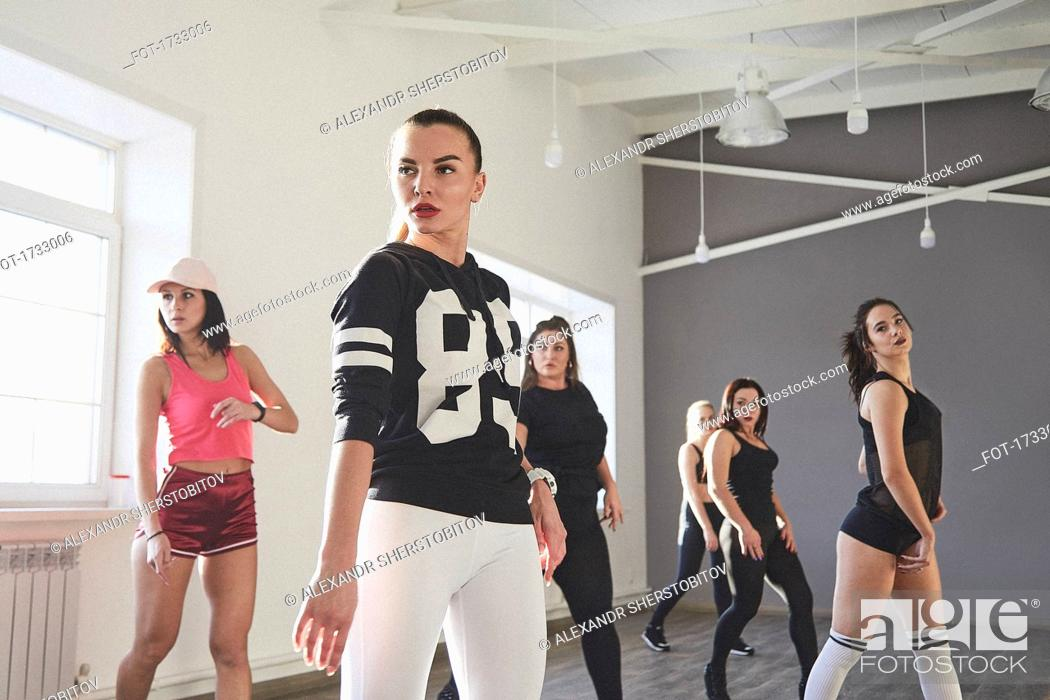 Stock Photo: Confident female friends dancing while practicing in dance studio.