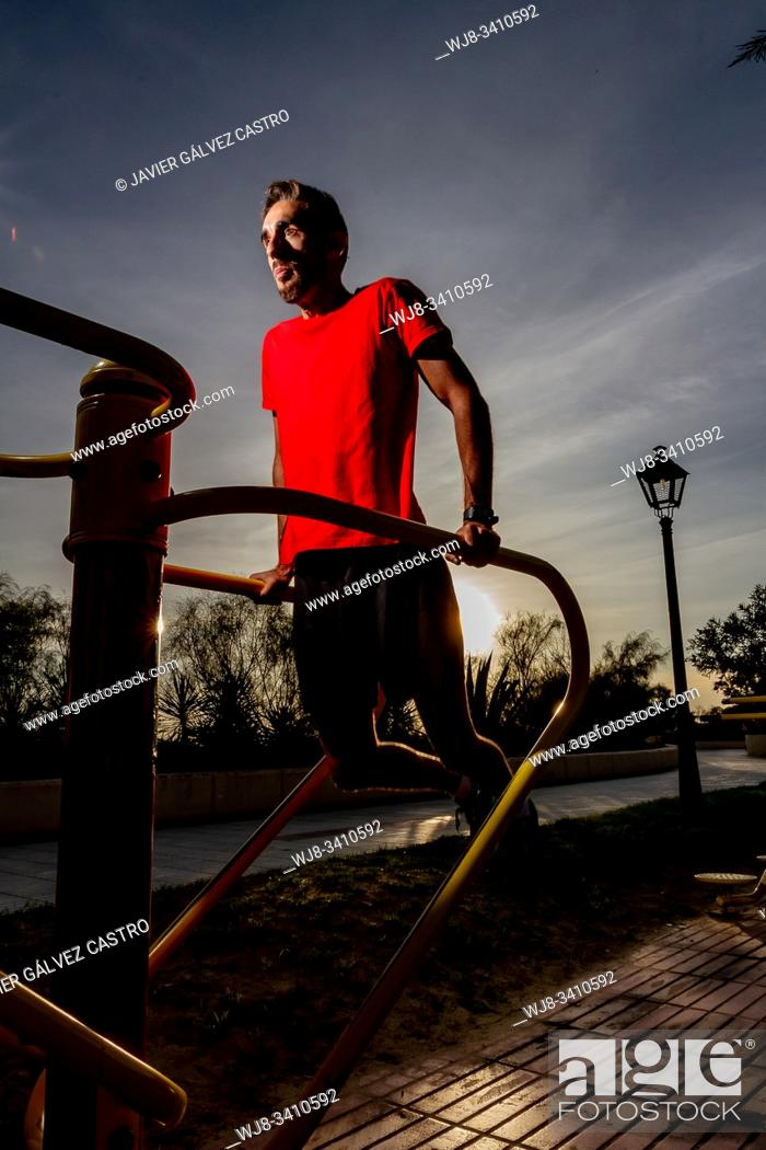 Stock Photo: athlete performing exercises on the machines placed on a promenade next to the beach at sunset.