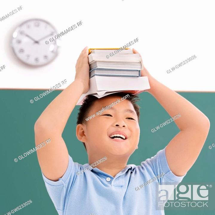 Stock Photo: Close-up of a schoolboy holding books on his head and smiling.